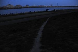 闇に包まれつつある荒川河川敷の緑の直線トラック