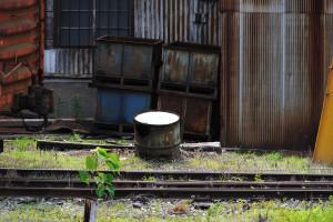 馬橋駅に隣接する工場のドラム缶が地面に半分埋もれた光景